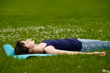 Girl Doing Yoga, Meditating, Shavasana Or Corpse Position In Park On Green Grass