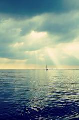 Fototapeta Rzeki i Jeziora Quiet after storm, sailboat with sun reflection on calm waters under a dramatic cloudscape