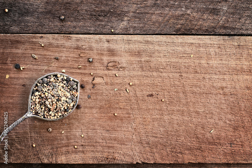 Fotografia, Obraz  Flatlay image of a tablespoon of pickling spices over a rustic wood plank background