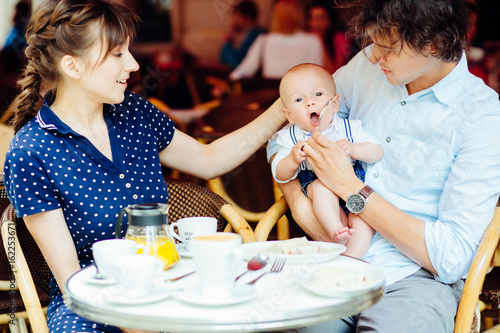 Young Happy Family Of Mother Father And Newborn Baby Boy Having Breakfast In The Street Cafe