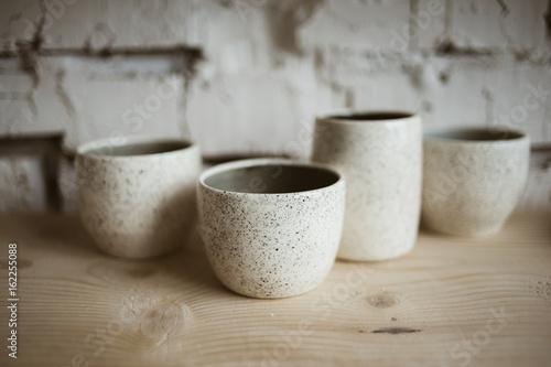 Pinturas sobre lienzo  Glazed white ceramic rustic cups on wooden shelf in pottery workshop
