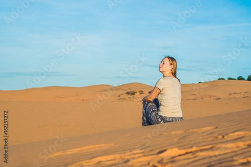 Foto op Aluminium Blauw young woman in rad sandy desert at sunset