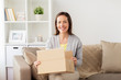 smiling woman opening cardboard box