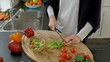 A woman preparing a salad. She is cutting cherry tomatoes. Lettuce, peppers, and radishes are strewn on the kitchen counter and cutting board.