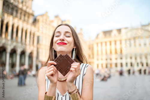 Young and happy woman with dark chocolate bar standing outdoors on the Grand place in Brussels in Belgium. Belgium is famous of its chocolate