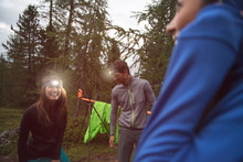 Happy Smiling Woman And Man With Headlamp Flashlight During Evening Near Camping. Group Of Friends People Summer Adventure Journey In Mountain Nature Outdoors. Travel Exploring Alps, Dolomites, Italy.