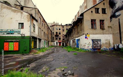 Opustoszałe Łódzkie podwórze, ze zrujnowanymi blokami i zniszczonymi witrynami Fototapeta