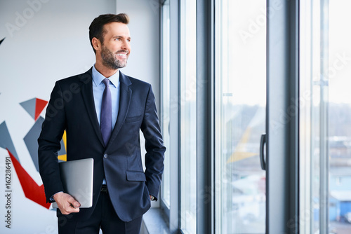 Portrait of middle-aged businessman looking through window while holding laptop