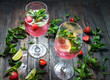 Strawberry cocktails with lime and ice cubes on rustic background