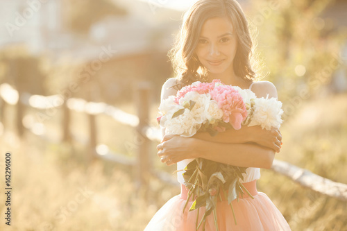 Fotografia  Beautiful young girl with peony on the nature outdoors in the sunshine