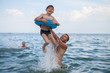 Dad and son bathe in the sea, play fun.