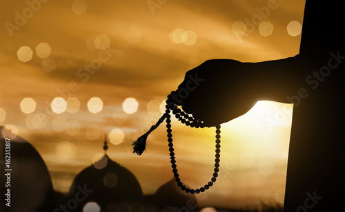 Silhouette muslim man praying with prayer beads