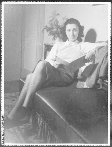 Woman Reads on Sofa. Date: 1940s Wallpaper Mural