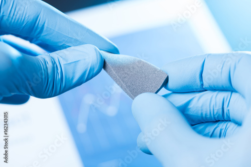 Scientist hand in gloves hold and bend small piece of gray porous foam, new type Canvas Print