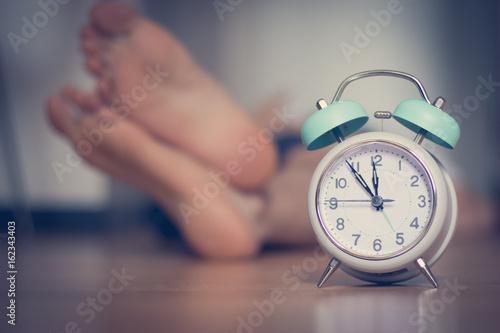 Plakat Śpiący człowiek, stopy i budzik