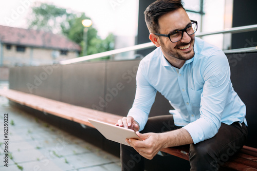 Fotomural Portrait of businessman in glasses holding tablet