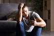 Sad man checking mobile phone