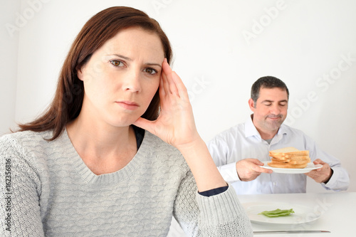 Fotografía  Young woman upset when her partner eat and enjoys carbohydrates