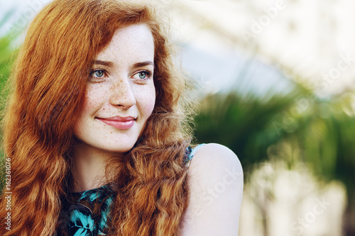 Outdoor close up portrait of young beautiful happy smiling redhead girl  with freckles 83679efd4
