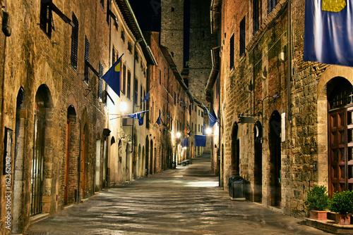 nocny-widok-na-oswietlona-uliczke-w-san-gimignano-we-wloszech