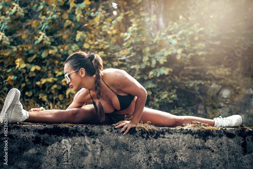 Fotografie, Obraz  Woman doing leg split in forest