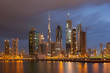 Dubai - The evening skyline with the bridge over the new Canal and Downtown with ths storm clouds.