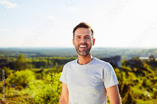 Fototapeta Portrait of happy adult man smiling outdoors obraz