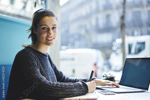 Fotografia  Portrait of charming young student sitting in coworking space looking at camera