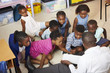 Teacher reading kids a book in an elementary school lesson