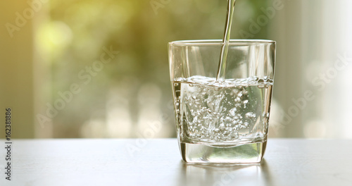 Canvas Prints Water Close up pouring purified fresh drink water from bottle on table in living room