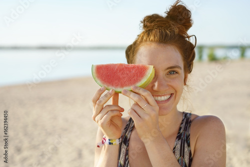 Cute young woman with a slice of watermelon