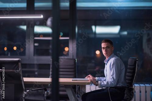 Fototapeta man working on laptop in dark office obraz na płótnie