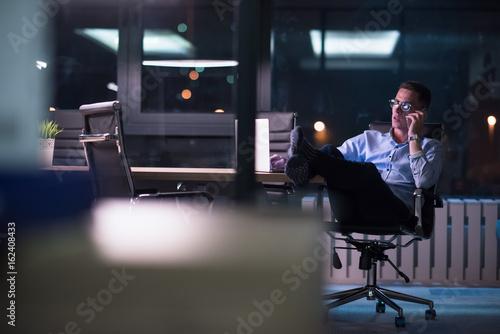 Fototapeta businessman using mobile phone in dark office obraz na płótnie