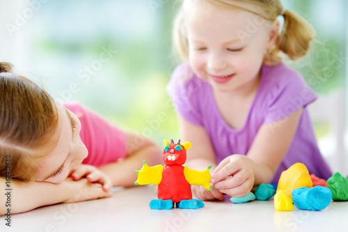 Two cute little sisters having fun together with colorful modeling clay at a daycare. Creative kids molding at home.