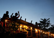 Silhouettes of people having fun on the rooftop of an outdoor club in late evening