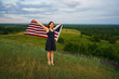 Proud woman with a US flag is standing on top of a hill