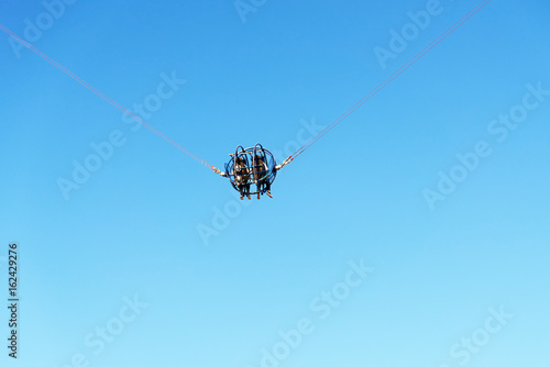 Poster Amusementspark Two people on a catapult cage in amusement park against blue sky.