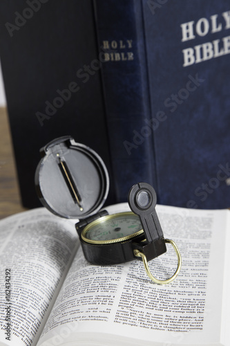 A compass laying on an open Bible