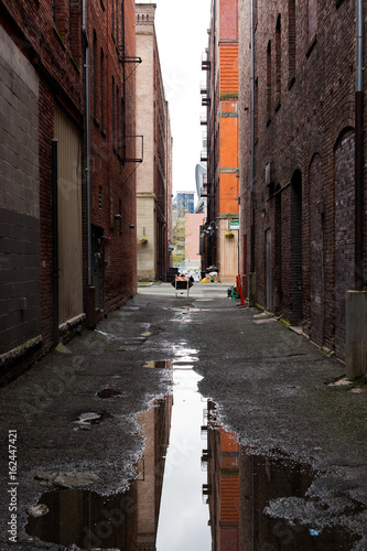 A reflective puddle in a dark alleyway