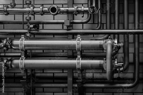 Pipes and valves against a wall make right angle Canvas Print