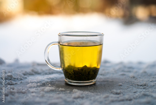 Staande foto Thee Tea with snow on wooden background table.
