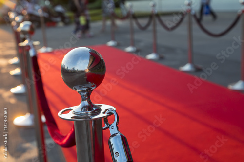 Photo  Long red carpet between rope barriers on VIP entrance.