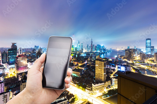 mobile phone with modern city at night Canvas Print