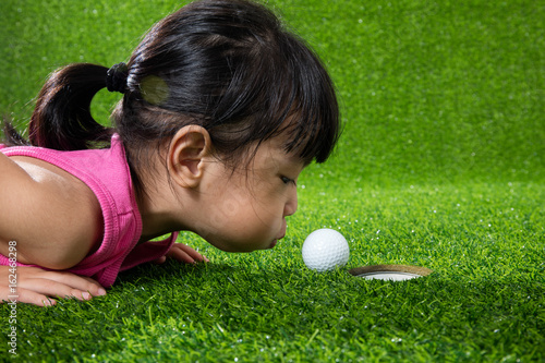 Fotografía  Asian Chinese little girl blowing the ball into a hole