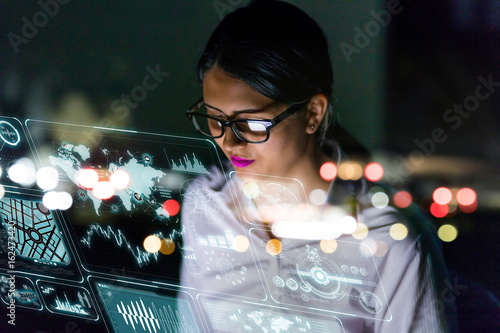 Fotografering  businesswoman looking at futuristic interface screen.