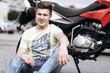 Young man sitting near the motorbike