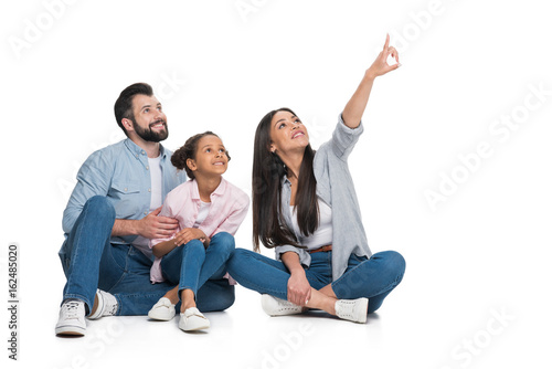 woman pointing away, family sitting near by and looking away isolated on white