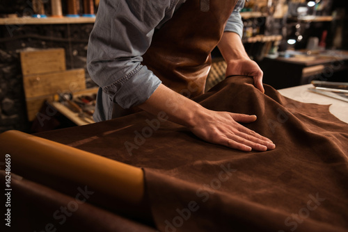 Photo  Close up of a cobbler working with leather textile