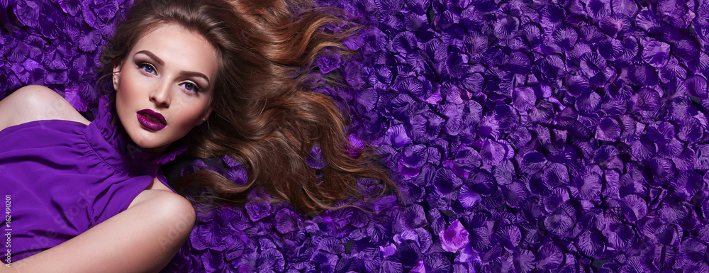 Fototapety, obrazy: The girl in the petals. Beautiful young girl lies in the violet petals in a long dress. Glamor, luxe. Hair - curls. Makeup - arrows, purple lipstick. Love, romance.