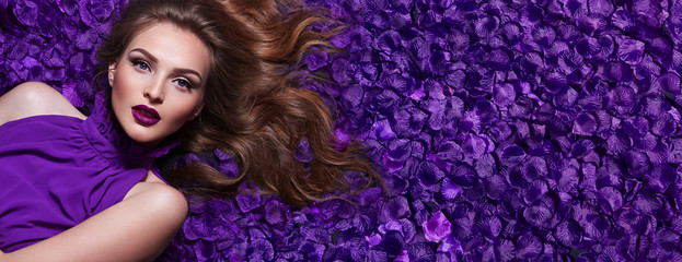 The girl in the petals. Beautiful young girl lies in the violet petals in a l...